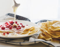 Crepes Pomegranate condensed Milk. Crepes with pomegranate and Condensed milk on kitchen towel, white background Royalty Free Stock Images