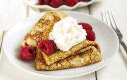 Crepes with raspberries and whipped cream. Crepes with fresh raspberries and whipped cream served on plate Stock Photo