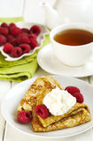 Crepes with raspberries and whipped cream. Crepes with fresh raspberries and whipped cream served on plate Stock Photos
