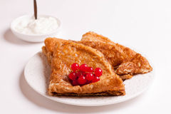 Crepes with red currants and sour cream on a plate isolated Stock Images