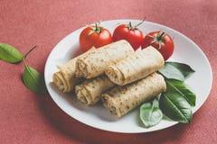 Crepes rellenas rodadas con los tomates Foto de archivo