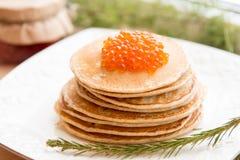 Crepes rusas con el caviar rojo en la placa Imagen de archivo