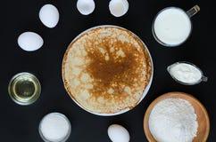 Crepes rusas con los ingredientes para cocinar en fondo negro Fotos de archivo