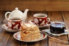 Crepes rusas en montón con el atasco y el té negro Foto de archivo libre de regalías