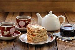 Crepes rusas en montón con el atasco y el té negro Foto de archivo