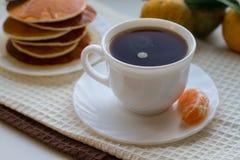 Crepes sabrosas con una taza de café en una tabla blanca Imagenes de archivo
