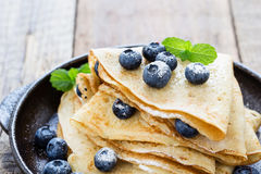 Crepes served with fresh blueberries and powdered sugar. Homemade crepes served with fresh blueberries and powdered sugar on rustic wooden table in cast iron stock photos