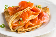 Crepes with smoked salmon. On a white plate Stock Image