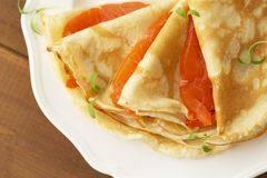 Crepes with smoked salmon on a white plate. Delicious and healthy Breakfast. Close up royalty free stock photography