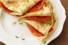 Crepes with smoked salmon on a white plate. Delicious and healthy Breakfast. Close up stock photography