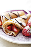 Crepes with strawberries. Sweet thin french style crepes, served with strawberries,chocolate sauce and caster sugar, very close up and very shallow dof for a Royalty Free Stock Photos