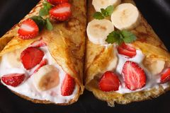 Crepes with strawberries, bananas and cream close-up. horizontal Stock Photography