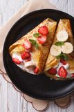 Crepes with strawberries, bananas and cream closeup vertical top Stock Photos