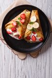 Crepes with strawberries, bananas and cream vertical top view Stock Photos