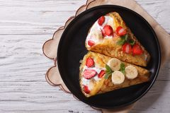 Crepes with strawberries and bananas horizontal top view Stock Images