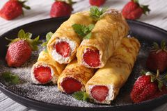 Crepes with strawberries and cream cheese close-up. Horizontal Stock Photos