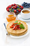 Crepes with strawberries and honey for breakfast, vertical Stock Image
