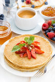 Crepes with strawberries and honey on white wooden background Stock Images