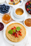 Crepes with strawberry, jams and honey on white background Royalty Free Stock Images