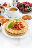 Crepes with strawberry, jams and honey on white background Royalty Free Stock Photography