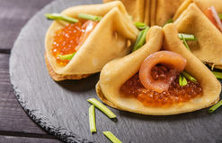 Crepes stuffed with caviar and salmon. On the shale plate Stock Images