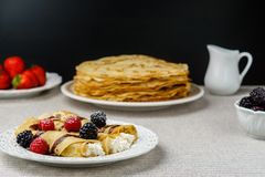 Crepes stuffed with cheese and berry topping on a plate for breakfast. stock photos