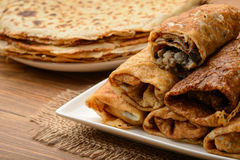 Crepes stuffed with chicken and mushrooms on wooden table. stock images