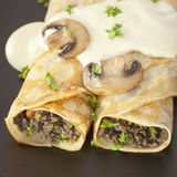 Crepes Stuffed with Mushrooms Pancakes. Crepes stuffed with mushroom duxelles and topped with bechamel sauce Stock Photos