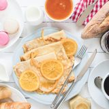 Crepes Suzette on blue plate, jam, baguette, coffee and macarons. Traditional french breakfast Royalty Free Stock Photography