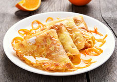 Crepes Suzette on white plate. Over wooden background Stock Photo