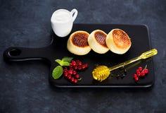 Crepes Syrniki con requesón, las bayas, la crema agria y la miel foto de archivo libre de regalías