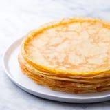 Crepes, thin pancakes, blini on a white plate. Marble background. Close up. Crepes, thin pancakes, blini on a white plate. Marble background. Close up royalty free stock photo