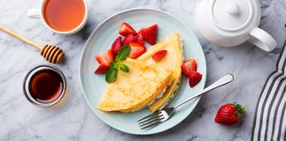 Crepes, thin pancakes with cream cheese, ricotta and fresh strawberries. Marble background. Top view. Crepes, thin pancakes with cream cheese, ricotta and fresh royalty free stock images
