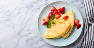 Crepes, thin pancakes with cream cheese, ricotta and fresh strawberries. Marble background. Top view. Copy space. Crepes, thin pancakes with cream cheese stock photography