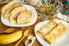 Crepes tradicionales en la placa blanca con los plátanos y el kiwi Fotografía de archivo