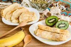 Crepes tradicionales en la placa blanca con los plátanos y el kiwi Imagen de archivo libre de regalías