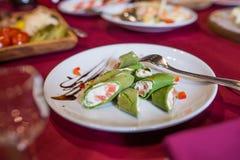 Crepes verdes Crepes con la espinaca rellena con el queso cremoso y los pescados en una placa blanca imágenes de archivo libres de regalías