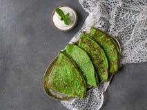 Crepes verdes da hortelã com a folha do creme de leite e da hortelã na placa de metal no fundo cinzento com tela do laço feche ac foto de stock