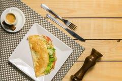 Crepioca - pannkaka av kassavatapiokor med tomater, letuce och ost på plattan på träbakgrund arkivfoton
