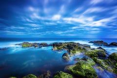 Crepuscolo sopra il mare blu calmo sopra l'oceano ed il cielo nuvoloso Immagini Stock