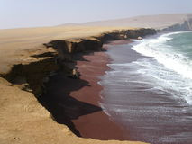 Crescent beach with dark brown sand. In the middle of the desert.  Paracas.  Peru Royalty Free Stock Images