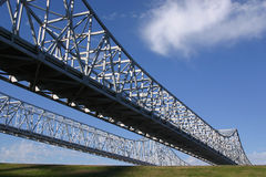 Crescent City Connection Bridges. The Crescent City Connection twin bridges in New Orleans rise across a levee in the foreground Royalty Free Stock Photography