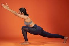 Crescent Lunge Forward Bend yoga pose. Woman show on orange color studio background royalty free stock photos