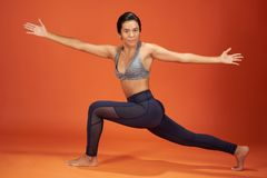 Crescent Lunge Twist yoga pose. Woman show on orange color studio background stock photo