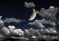 Crescent and many clouds in night sky Royalty Free Stock Image