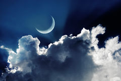 Crescent moon in a beautiful night sky with glowing clouds royalty free stock photo