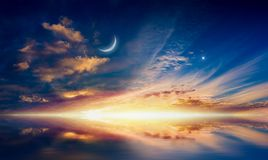 Crescent moon, glowing clouds and bright star. Amazing surreal background - crescent moon, glowing clouds and bright star are reflected in serene sea. Elements royalty free stock photography