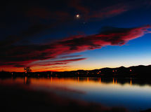 Crescent Moon - Jupiter - Venus Conjunction. Sunset conjunction reflected in calm evening lake royalty free stock image