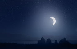 Crescent moon over the city Stock Photos