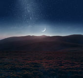 Crescent moon over the mountains. Mountain scene with twilight sky, Moon and shining stars of Milky Way Stock Photography